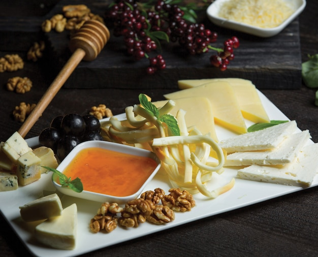 White ceramic cheese plate with different kinds of cheese, nuts and honey