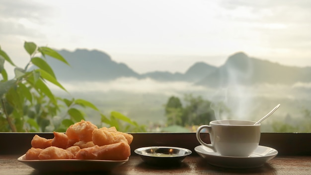 White ceramic coffee cup and fried phongko food on wooden table  in morning with sunlight, blurred mountains landscape, asian breakfast concept