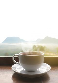 Белая керамическая кофейная чашка на деревянном столе утром с солнечным светом над затуманенное горы пейзаж