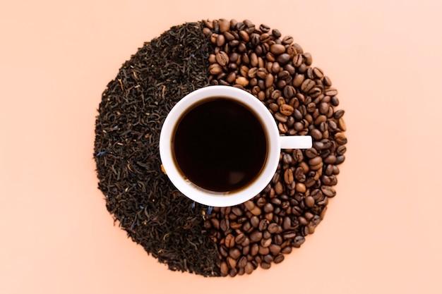 白いセラミックコーヒーカップ、焙煎したコーヒー豆、乾燥した茶葉。