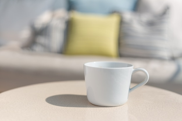 White ceramic coffee cup on white ceramic table on sunny day