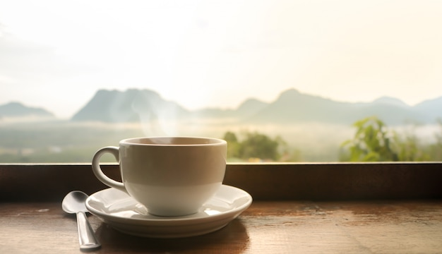 White ceramic coffee cup on wooden table  in morning with sunlight over blurred mountains landscape