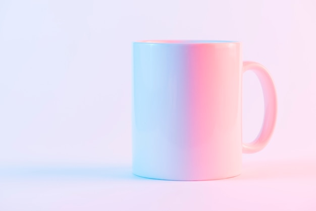 White ceramic coffee mug against pink backdrop