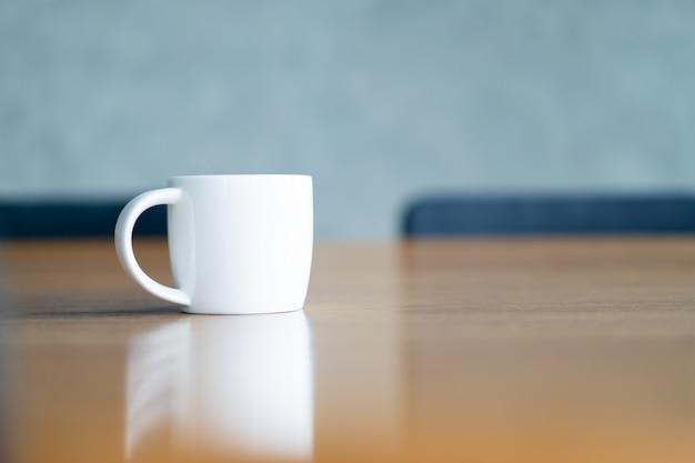White ceramic coffee mug on the table in coffee bar with .  coffee mug copyspace.