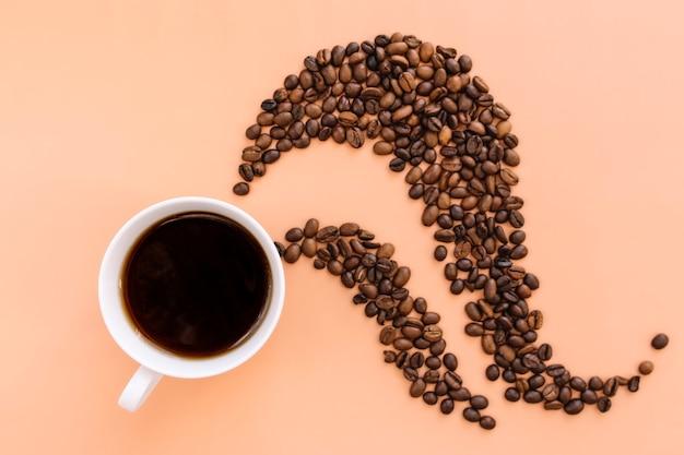 白いセラミックカップのコーヒー、焙煎したコーヒー豆はホットコーヒーから形を蒸します。 Premium写真