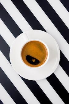 ストライプの濃いコーヒーの白いセラミックカップ。ミニマリズムのモーニングコーヒー