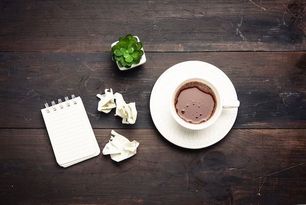 White ceramic cup with black coffee on brown wooden table, top view
