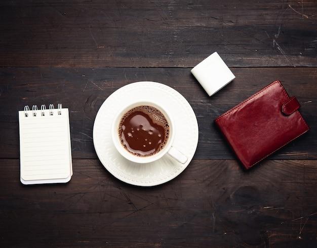 ブラックコーヒー、革の茶色の財布、木製の茶色のテーブルにワイヤレスヘッドフォン、上面図と白いセラミックカップ