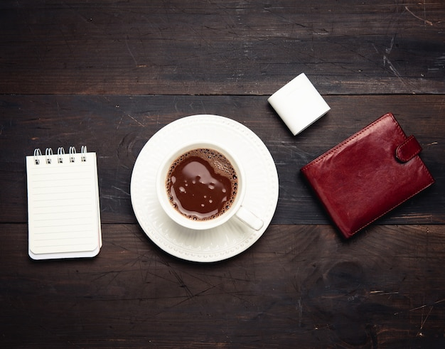 White ceramic cup with black coffee, leather brown wallet and wireless headphones on a wooden brown table, top view