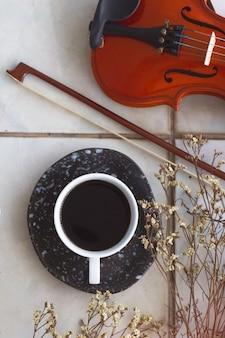 Белая керамическая чашка с черным кофе рядом с сушеным цветком, смычком и скрипкой. на заднем плане