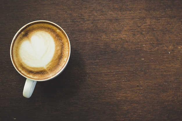 White ceramic cup with black coffee on wood background