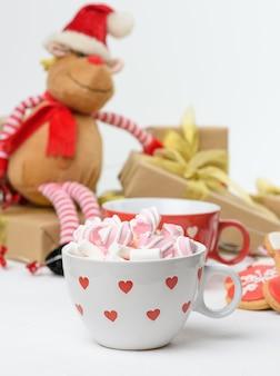 ギフトボックスとクリスマスのおもちゃの後ろに、ココアとマシュマロの白いセラミックカップをクローズアップ