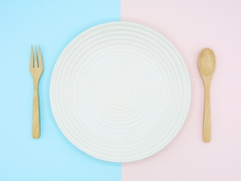 White ceramic dish on blue and pink paper - background
