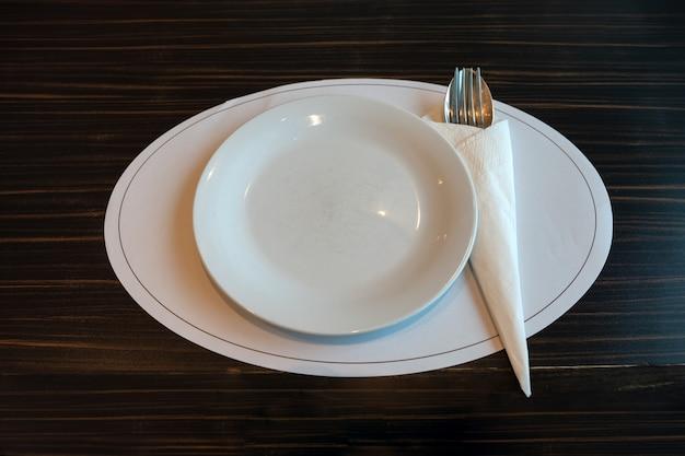 Белое керамическое блюдо с ложкой, вилкой и салфеткой на деревянном столе в ресторане
