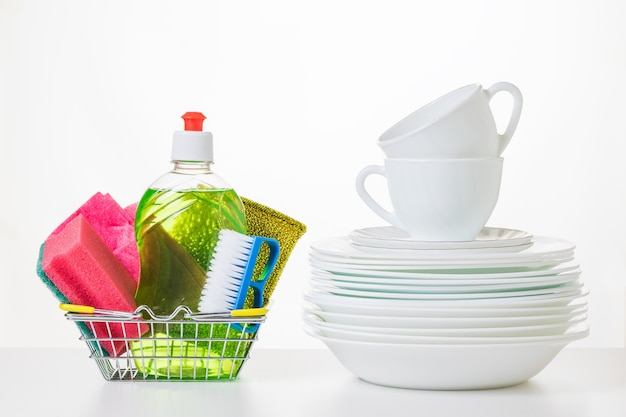 White ceramic dishes and detergents on a light surface