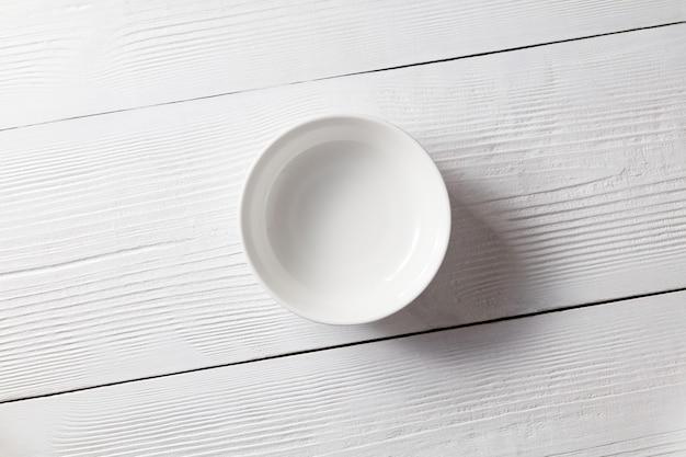 Белая керамическая пустая тарелка на белом деревянном столе