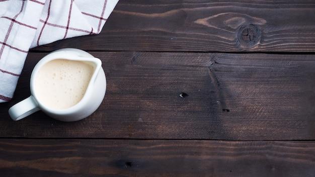 White ceramic milk jug with fresh milk. dark wooden rustic table.