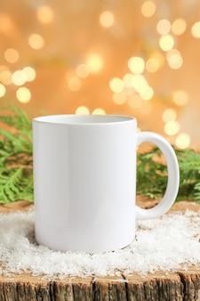 コピースペースのための雪と氷のモックアップの断片と木製のテーブルの上の白いセラミックマグカップ