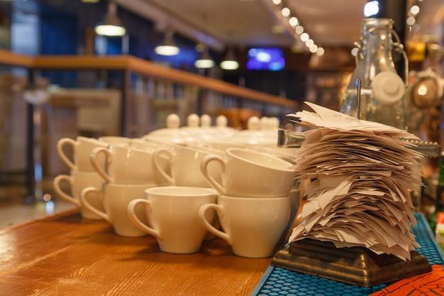 Белые керамические кружки для чая и чеки по выполненным заказам в баре или на кухне ресторана, насаженные на острую тонкую железную иголку на подставке. концепция проверки, стенд для проверки, флажок