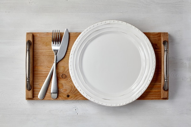 白いセラミックプレートと薄い塗装の木製テーブルにカトラリー付きのトレイ