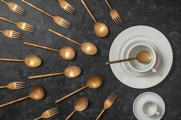 White ceramic plate, cup and brass forks and spoons look like sperm competition. spermatozoons floating to ovule. concept of fertilization, pregnancy and contraception. top view, close up