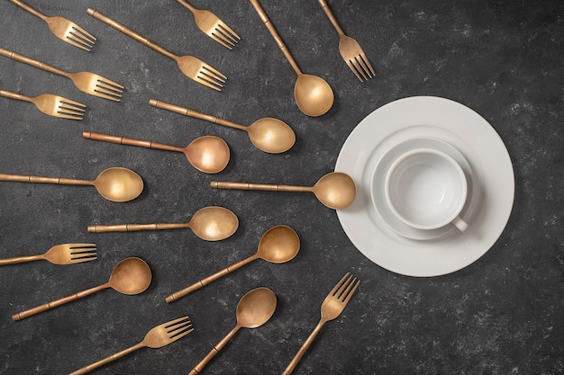 White ceramic plate, cup and brass forks and spoons look like sperm competition.