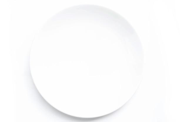 白いテーブルの上の白いセラミックプレート。食品、広告スペース。