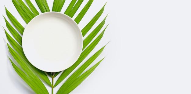 Белая керамическая пластина на тропических пальмовых листьев на белом фоне.