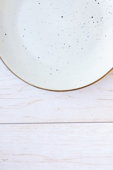 Белая керамическая тарелка на деревянной поверхности, вид сверху