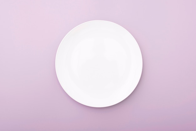 White ceramic plate on pink table, top view of white dish. round plate, bowl.