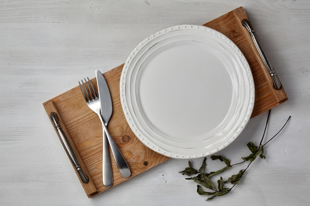 A white ceramic plate and a tray of cutlery on a light painted wooden table