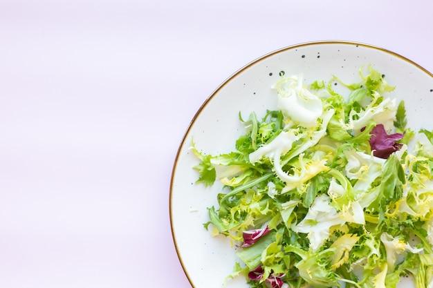 Белая керамическая тарелка со свежим салатом на светло-розовой поверхности