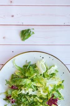 Белая керамическая тарелка со свежим салатом на деревянной поверхности
