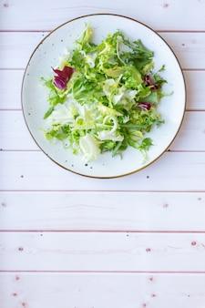나무 표면에 신선한 샐러드와 화이트 세라믹 플레이트