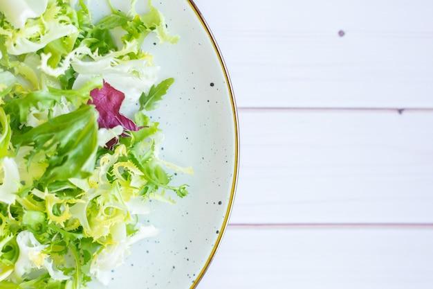 Piatto in ceramica bianca con insalata fresca su una superficie di legno