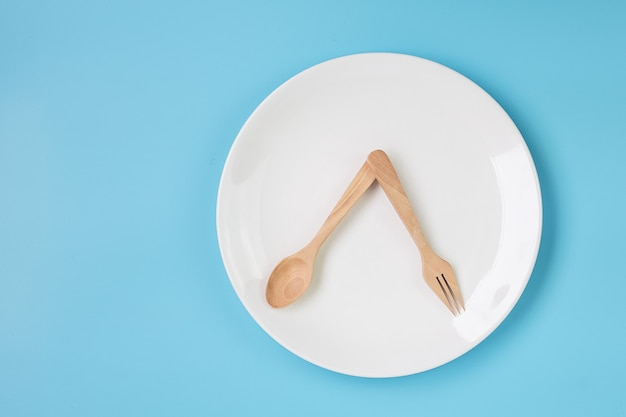 Белая керамическая тарелка с ножом, ложкой и вилкой на синем фоне. концепция прерывистого голодания