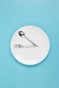 Белая керамическая тарелка с ножом, ложкой и вилкой на синем фоне