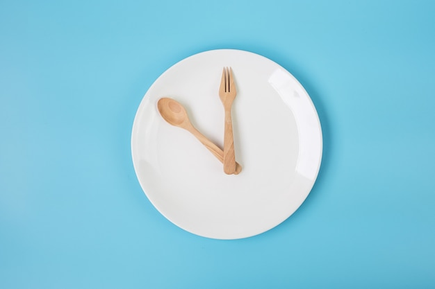 White ceramic plate with knife, spoon and fork on blue background. intermittent fasting concept