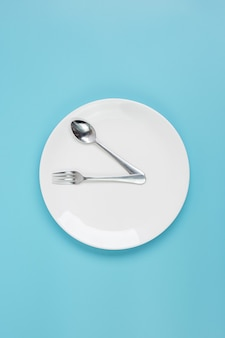 White ceramic plate with knife, spoon and fork on blue background