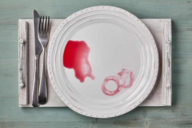 Белая керамическая тарелка с пролитым ягодным соусом и столовыми приборами на белом деревянном подносе. макет меню ресторана