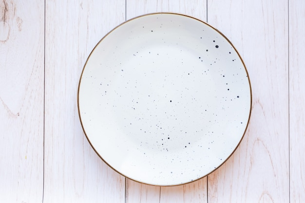 Piatto in ceramica bianca su superficie in legno, vista dall'alto
