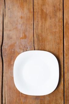 ヴィンテージの木製テーブルの上の白いセラミックの四角い皿