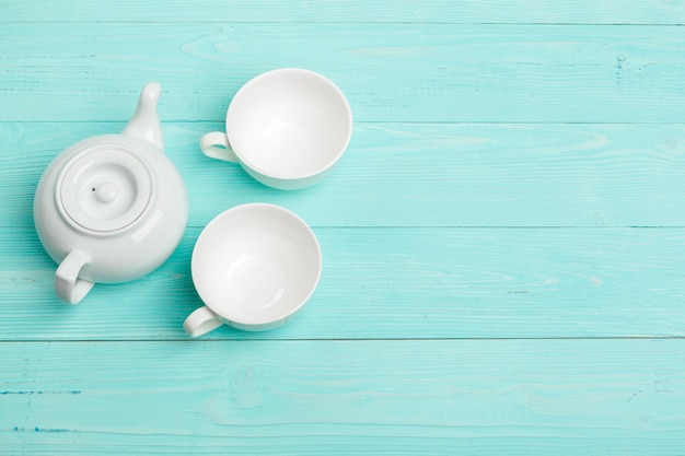 White ceramic tea kettle on wooden table close up