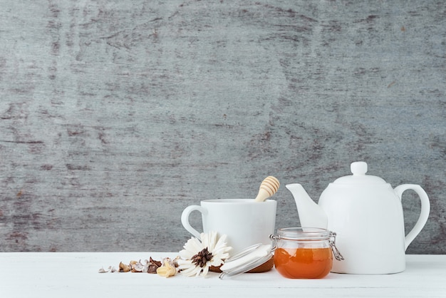 White ceramic teapot, cup and honey in glass jar on a wooden with copy space