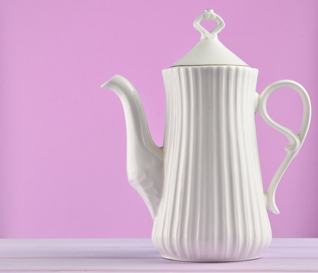 White ceramic teapot on a pastel purple wooden table isolated on purple background