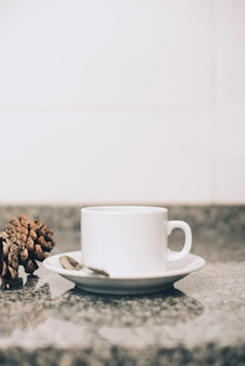 White ceramics cup and saucer on reflective marble table