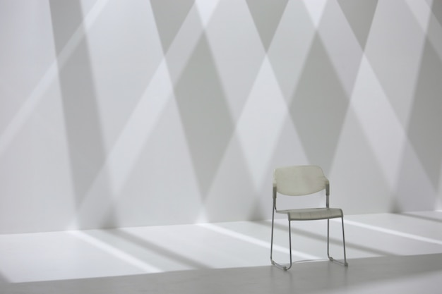 White chair in front of diamond shape shadow wall