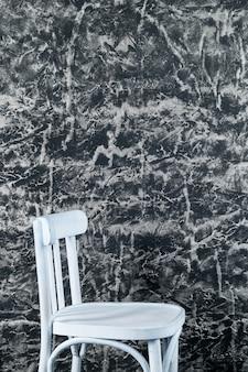 Белый стул возле текстуры декоративной венецианской лепной стены