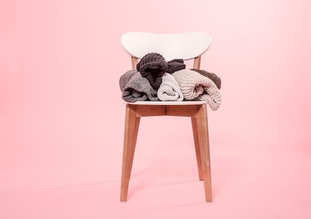 Белый стул со стопкой вязаных свитеров на розовом фоне