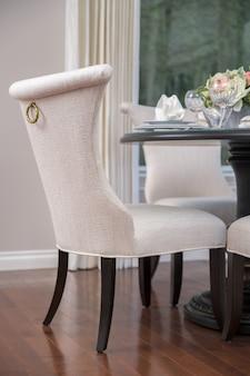 リビングルームに花のテーブルと白い椅子